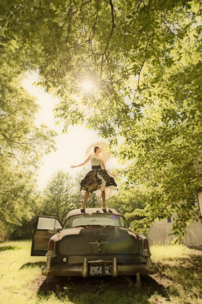 Woman standing on roof of car, under trees
