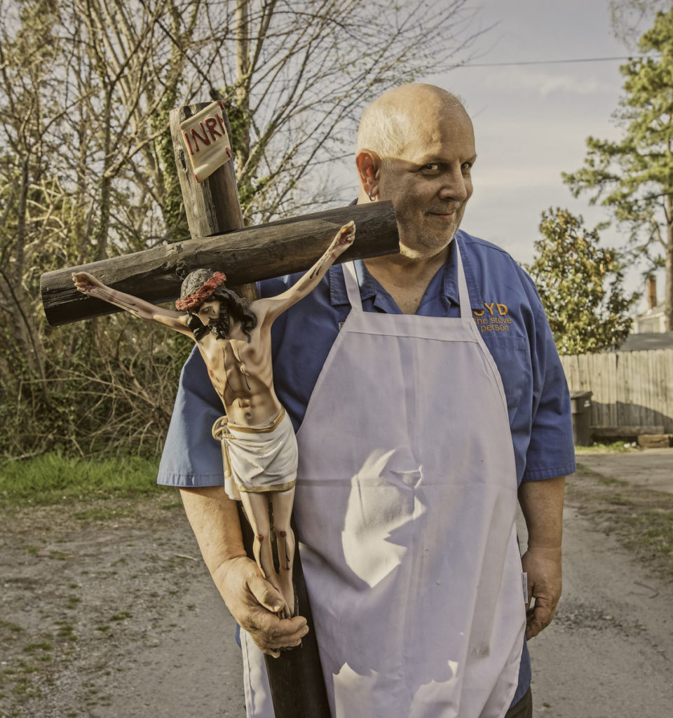 Man holding large cross with Jesus on it