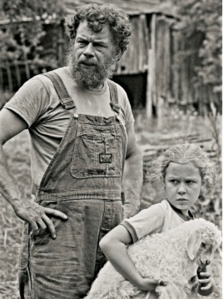 Man in overalls and young girl holding a lamb