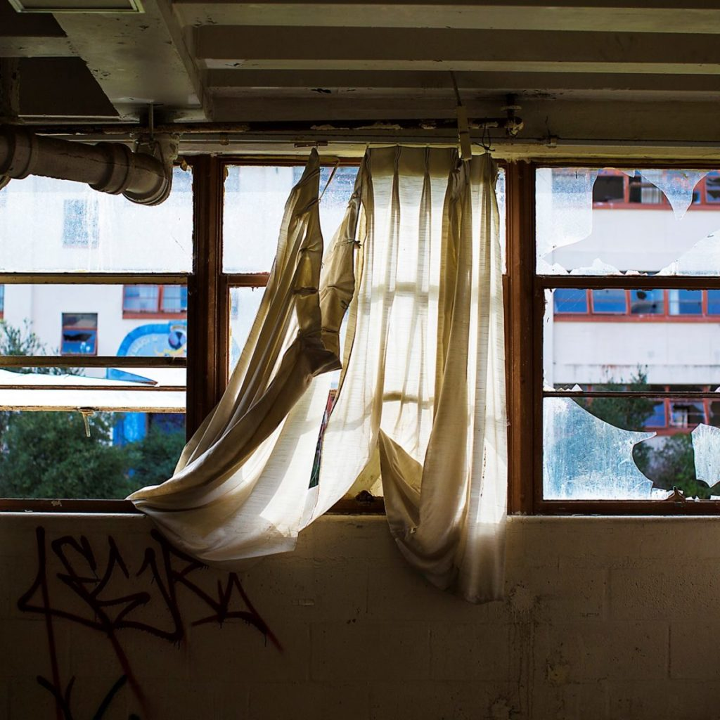 Photo of wall with broken windows and torn curtains