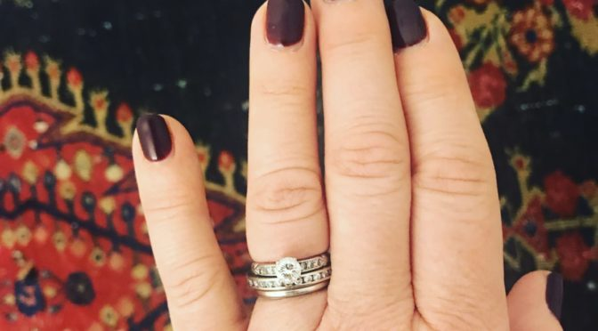 Photo of hand with wedding rings on ring finger