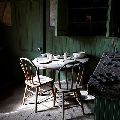 Photo of a dusty kitchen, table and chairs