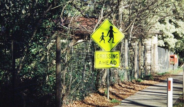 Photo of child crossing sign ahead and narrow sidewalk