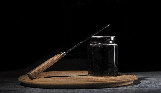 Jar of dark jam with a knife set against black background