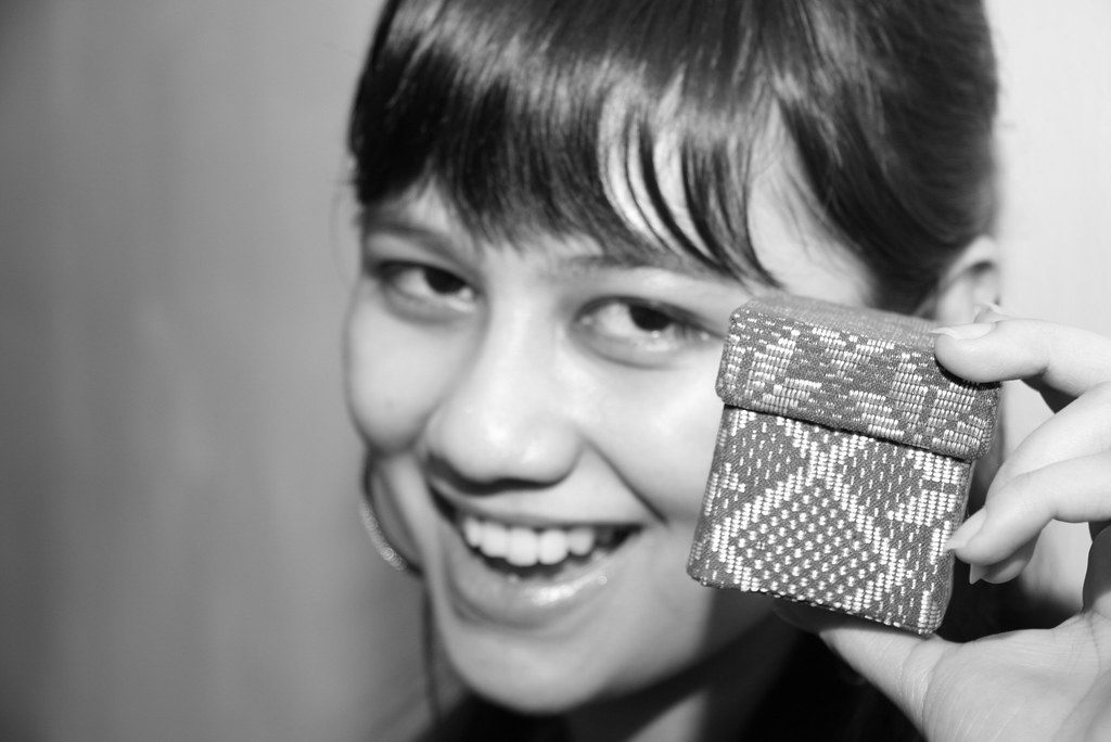 Black & white photo of woman holding small box