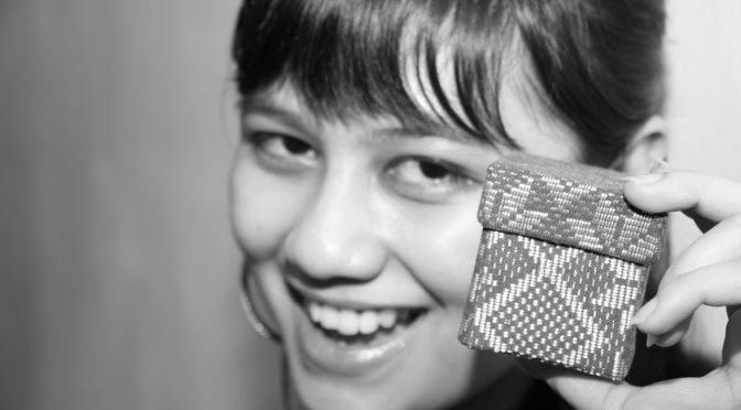 Black & white photo of woman holding small box