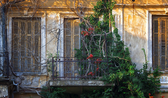 Color photo old home with balcony and vines