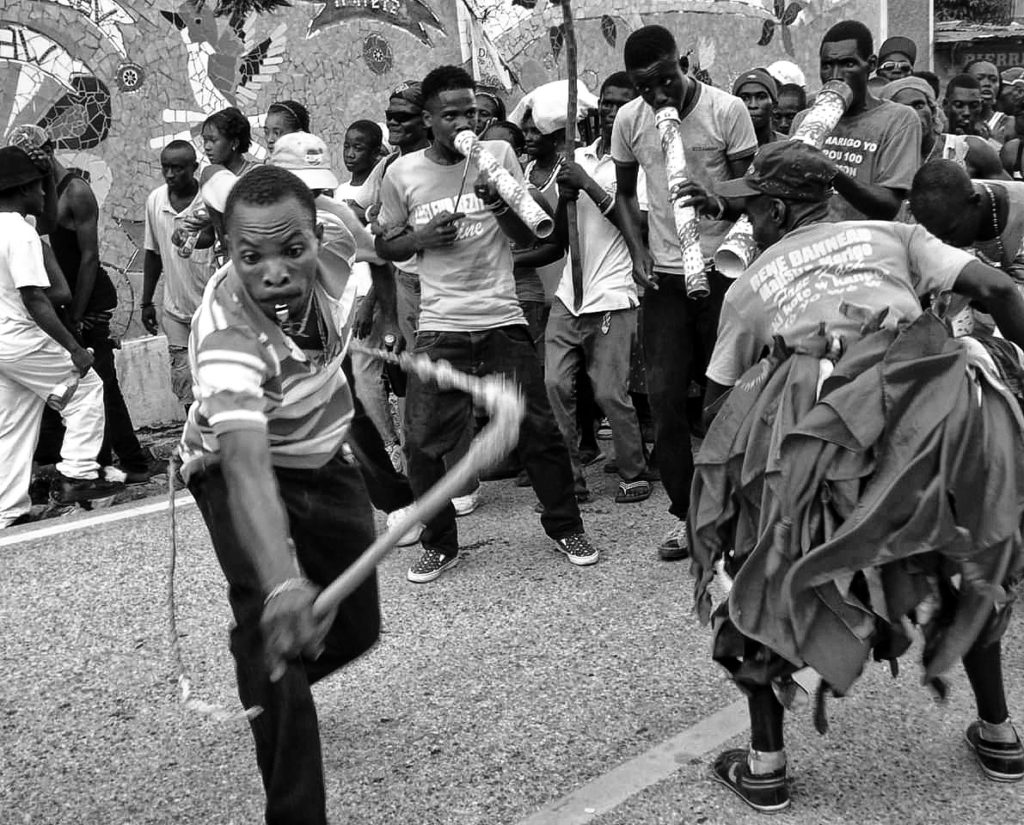 Black and white photo of people dancing, parading