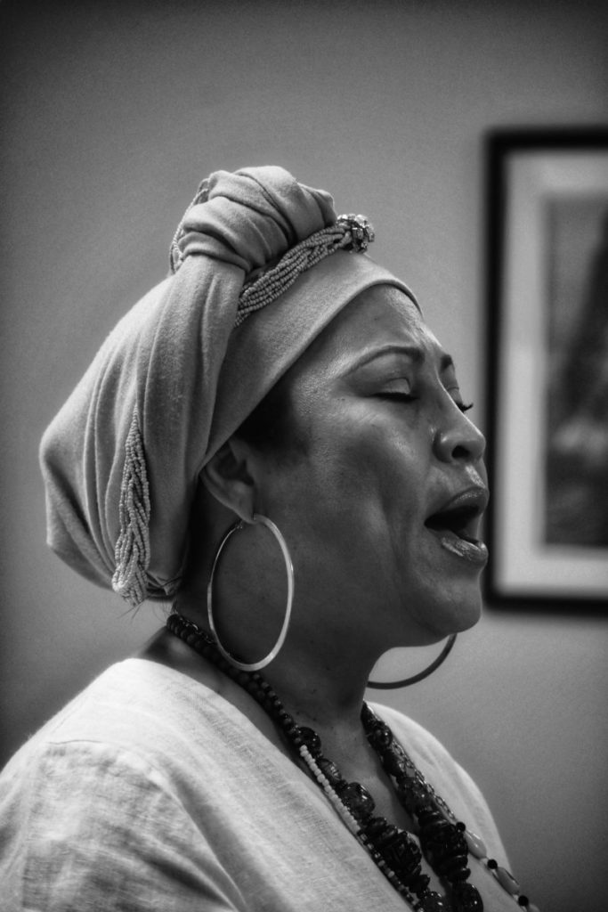 Black and white photo of woman with eyes closed, talking or singing