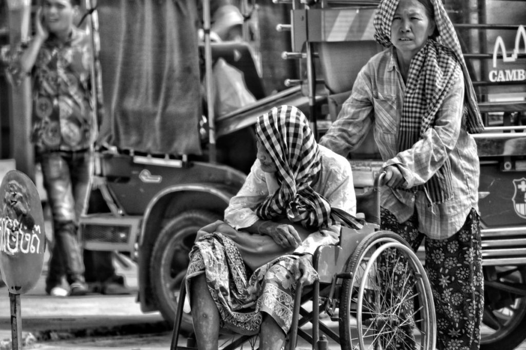 Black and white photo of woman being pushed in wheelchair