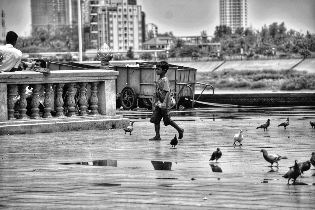 Black and white photo of boy walking through pigeons
