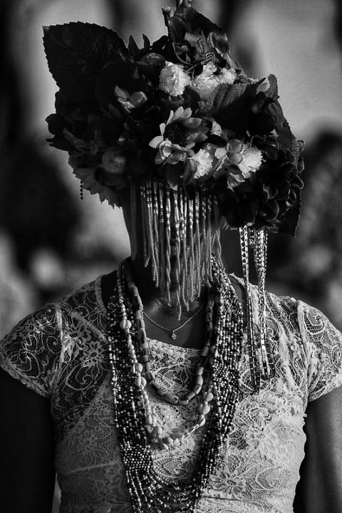 Black and white photo of woman with headress covering face