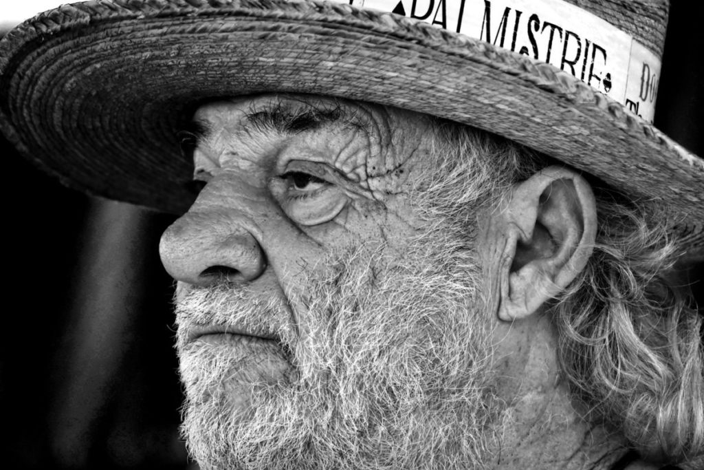 Black and white photo of older man in hat