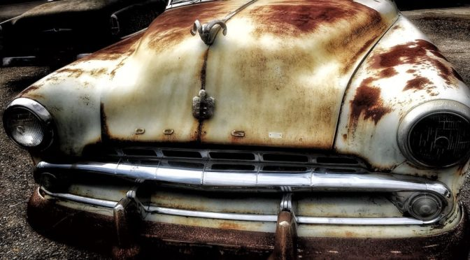 Photo of white, rusty old Dodge