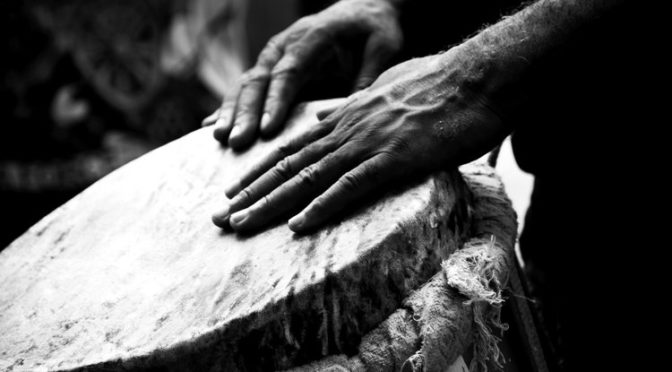 Black and white photo of hands playing a drum