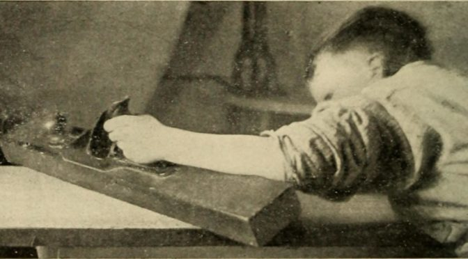 old 1900 photograph of a boy planing a piece of wood