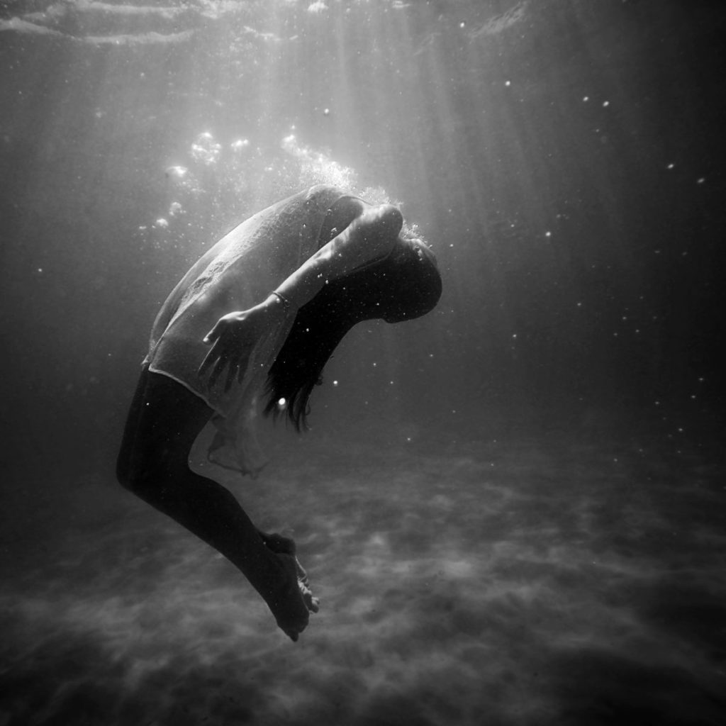 Black and white photo of woman underwater