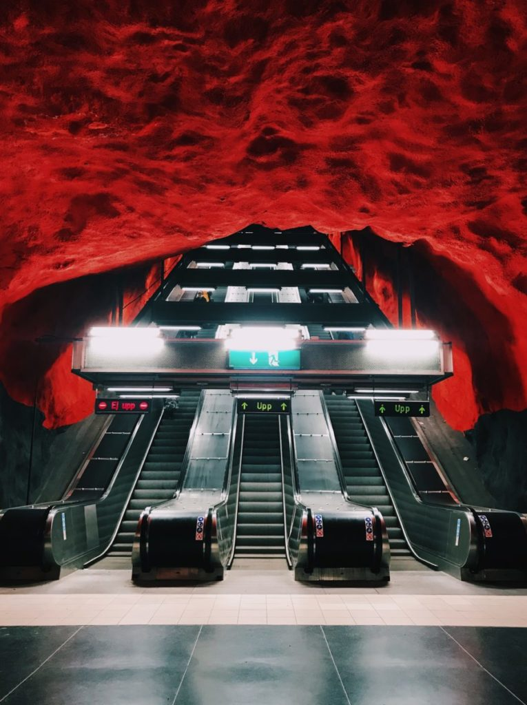 Escalators and building leading to a red tunnel