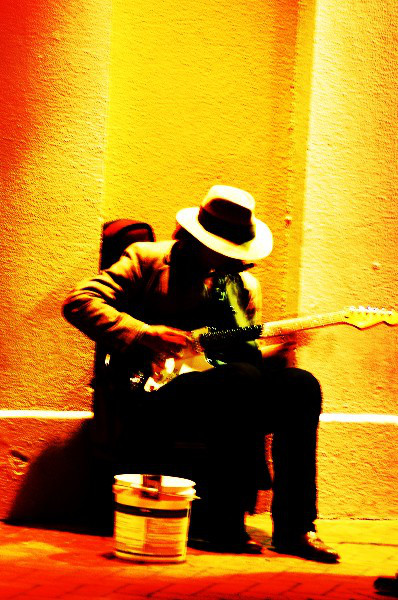 Man playing guitar on sidewalk