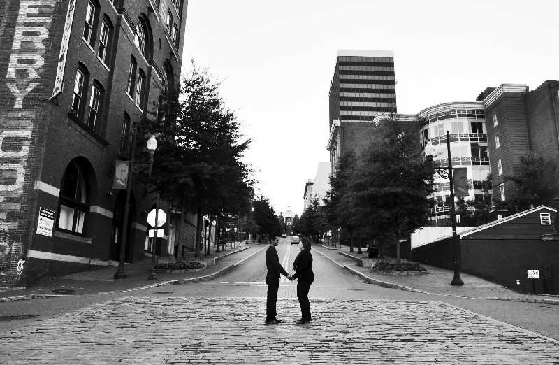 Couple holding hands, facing each other, in middle of street