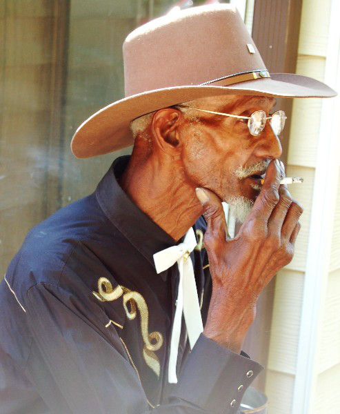 Older man in cowboy hat smoking