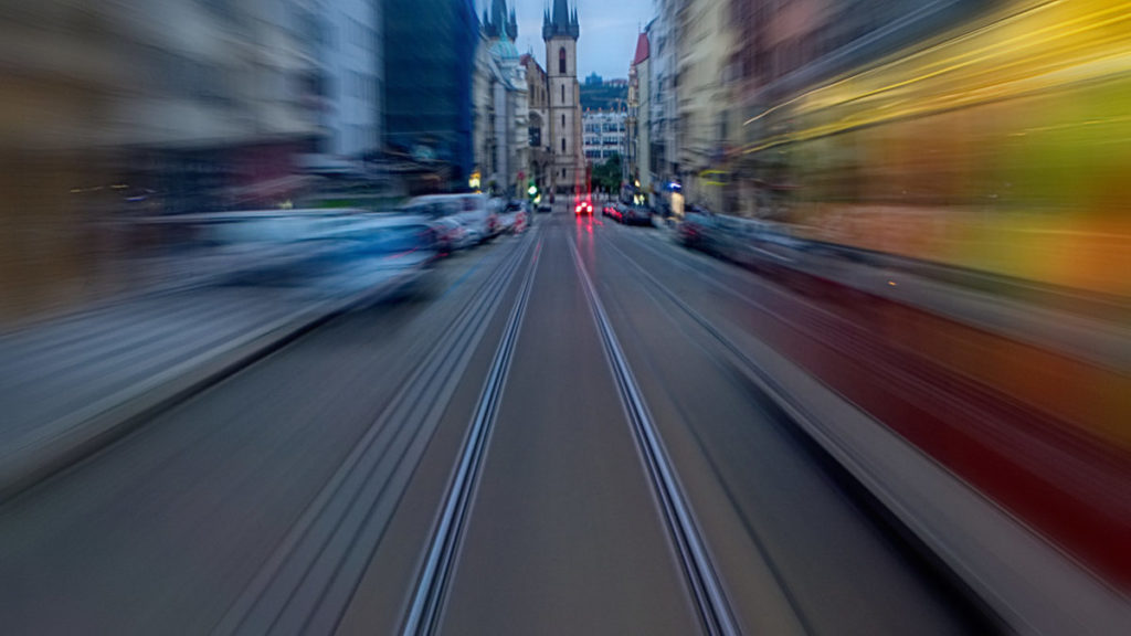 A tram speeding down a blurred narrow street