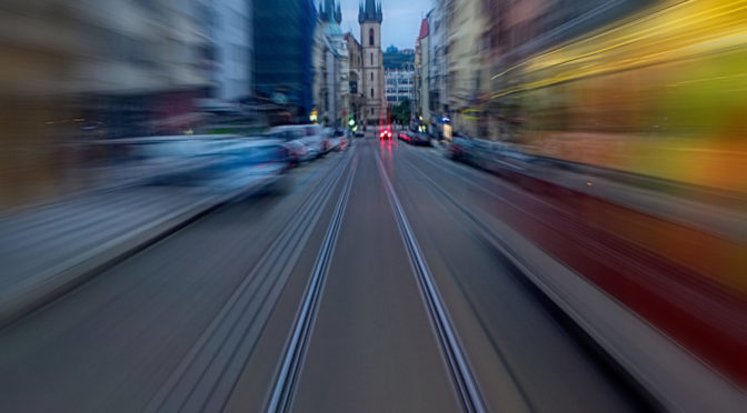 A tram speeding down a blurred narrow street