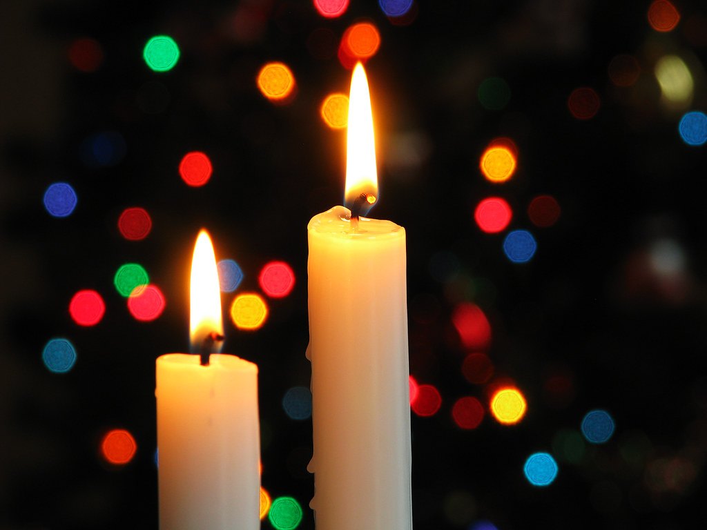 Lit candles and blurred colored lights