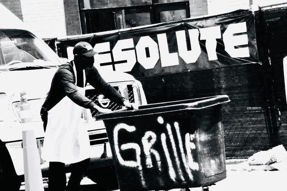 Black and white photo of man pushing trash bin