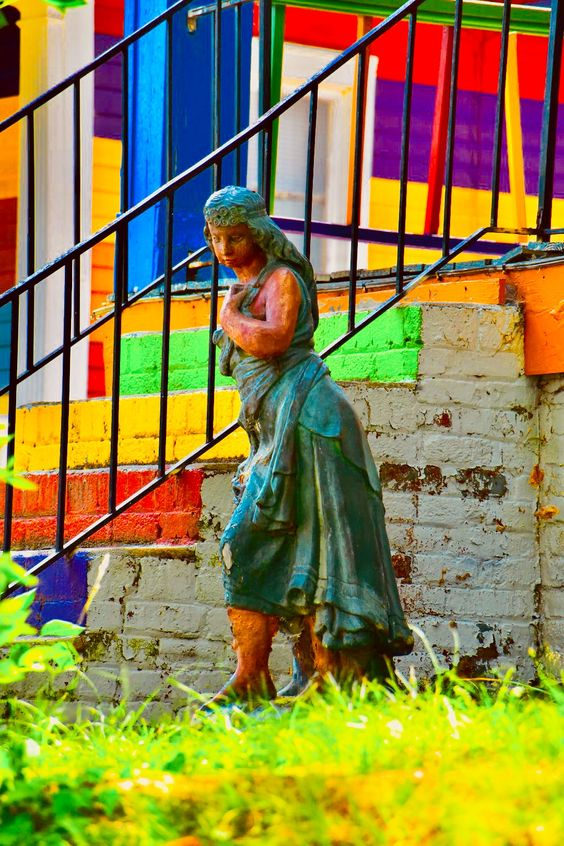 Photo of statue in front of rainbow colored house
