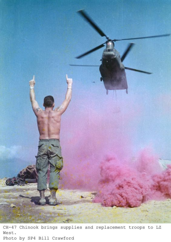 Photo of man standin in miltary pants under helicopter