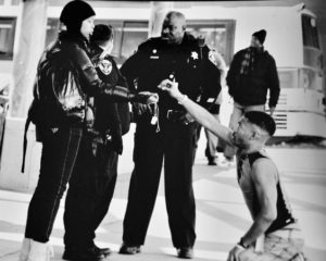 Black and white photo of man on knees in front of cops