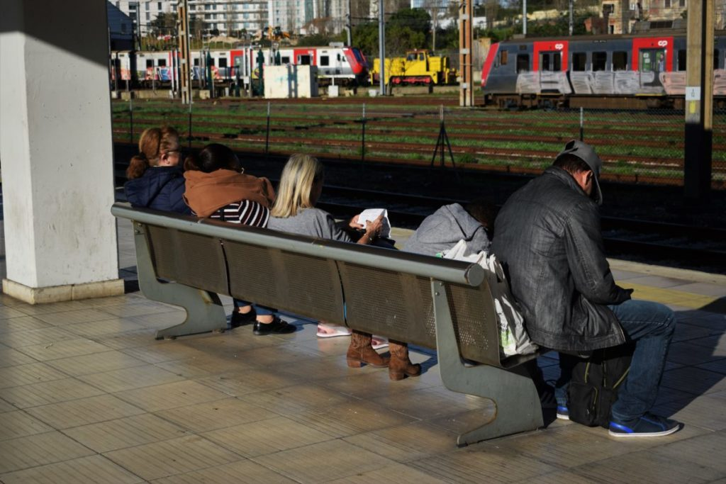 Many people sitting on public bench
