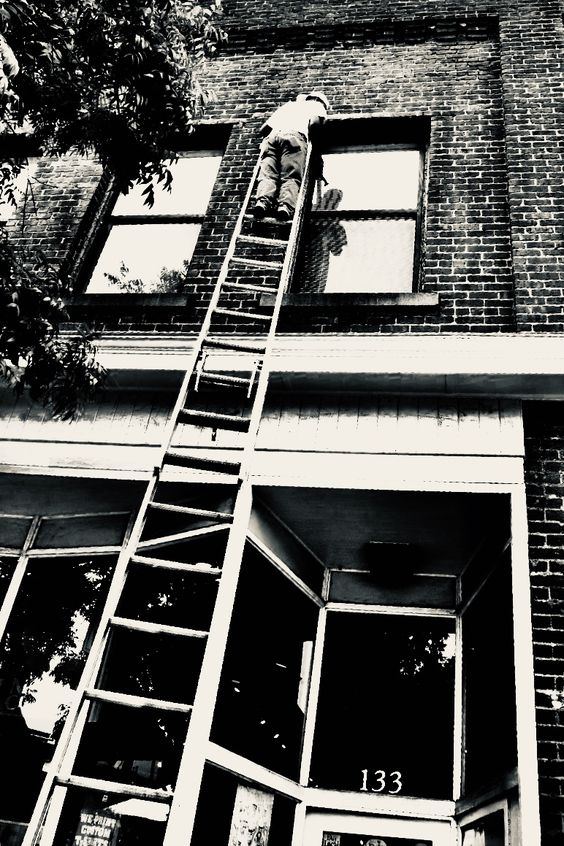 Black and white photo of window washer on ladder