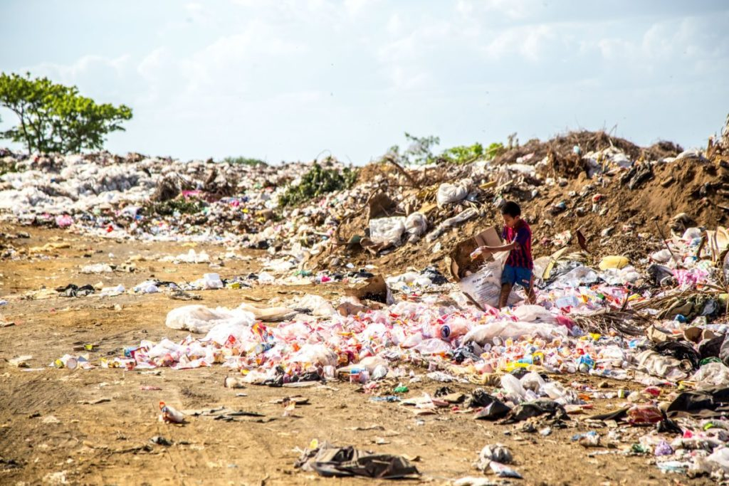 Photo of person in large trash pile