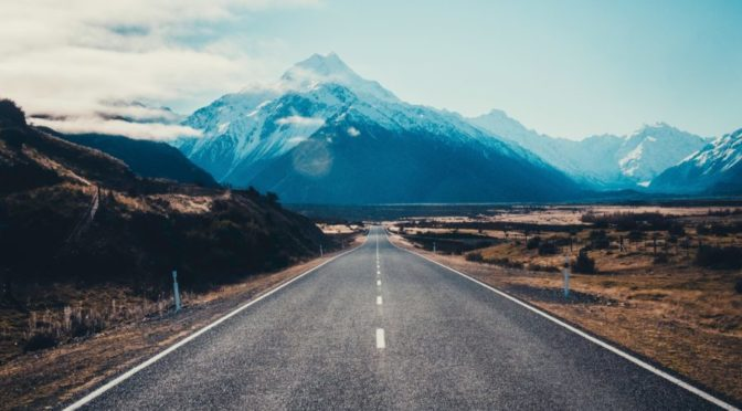 Photo of road leading to mountains and blue sky