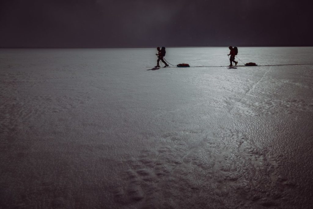 Two skiers in vast, dark, snowy landscape