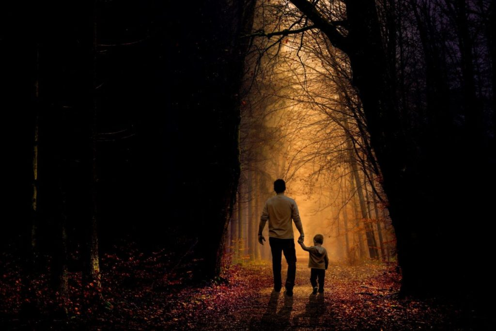 Father and son walking through an opening of light between trees