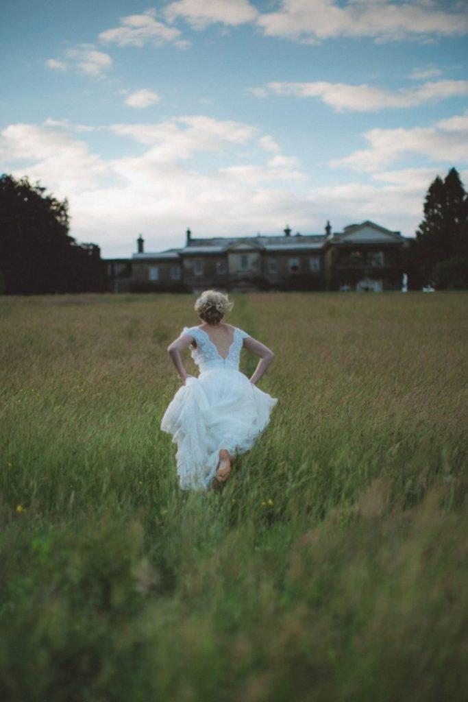 Photo of woman in wedding dress running through field