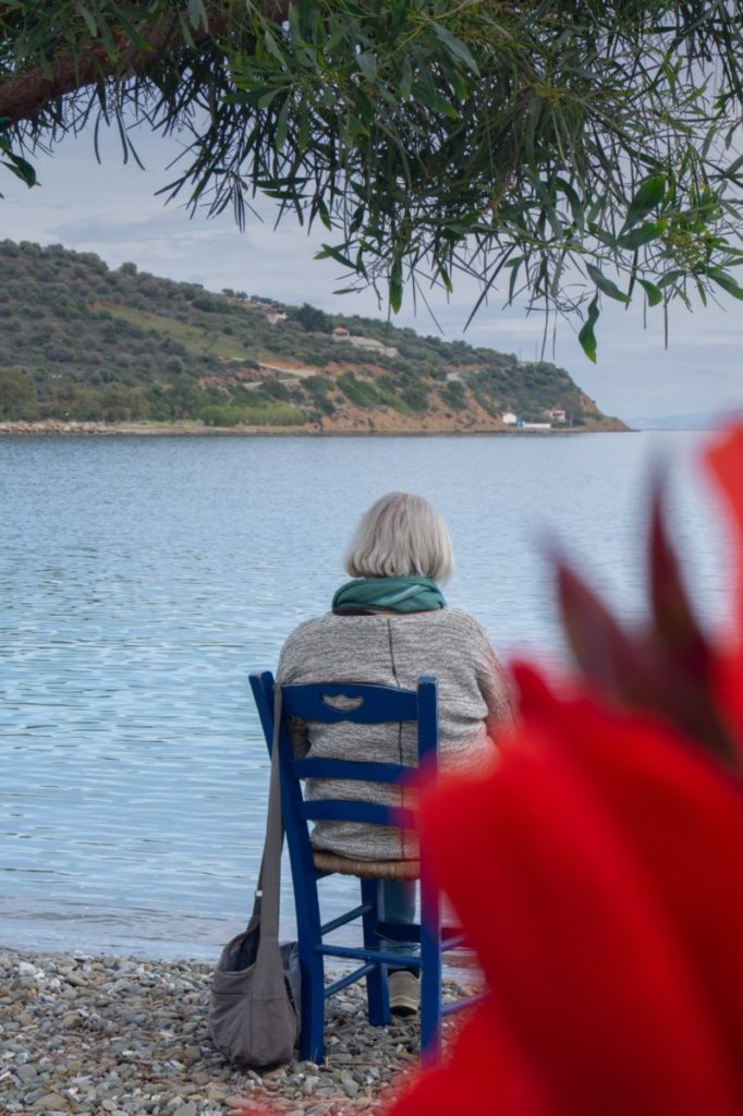 Photo of woman sitting in chair facing water