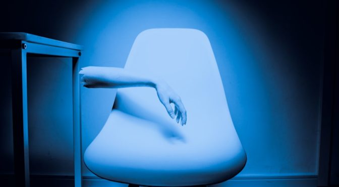 Abstract photo of chair with part of arm hanging over it