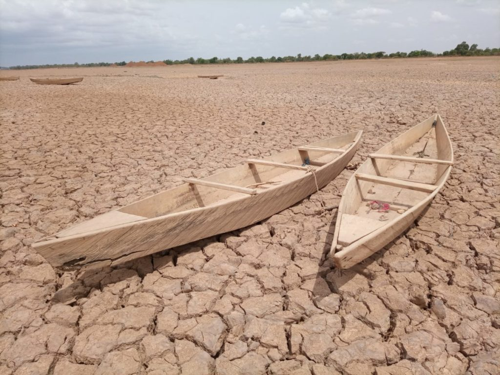 Photo of two canoes on dry, cracked earth