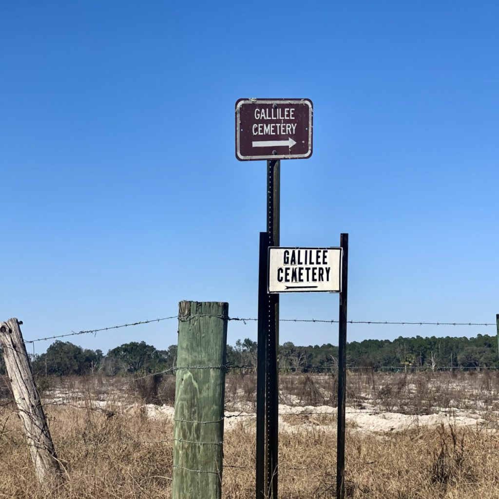 Dusty terrain, fence post reading Gallilee Cemetery