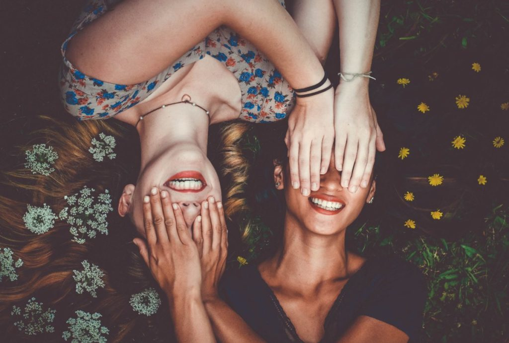 Two girls, covering each other's eyes