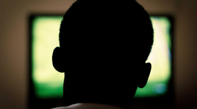 Silhouette of man's head in front of tv