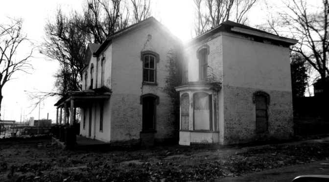 Photo of old house with light shining over it