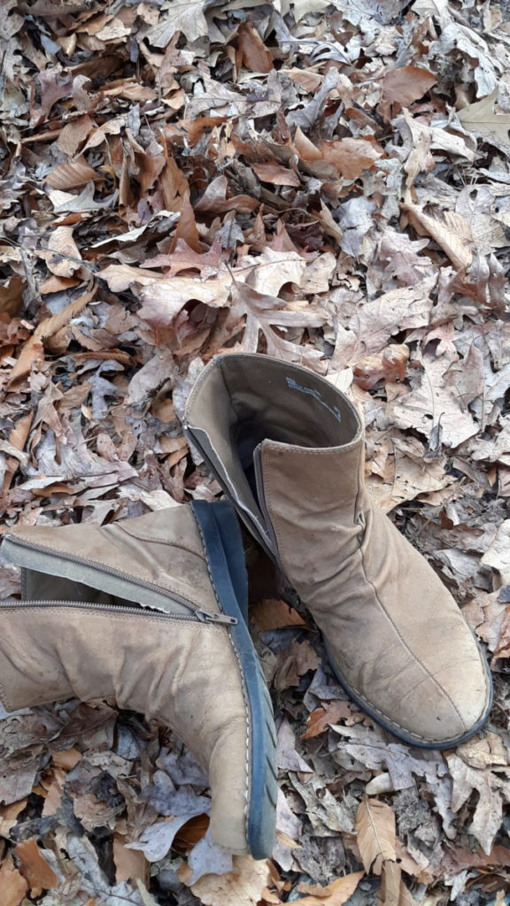 worn brown boots in leaves