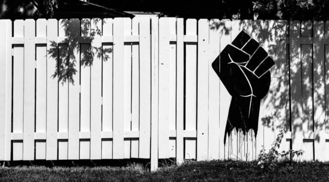 Black and white photo of black fist painted on white fence