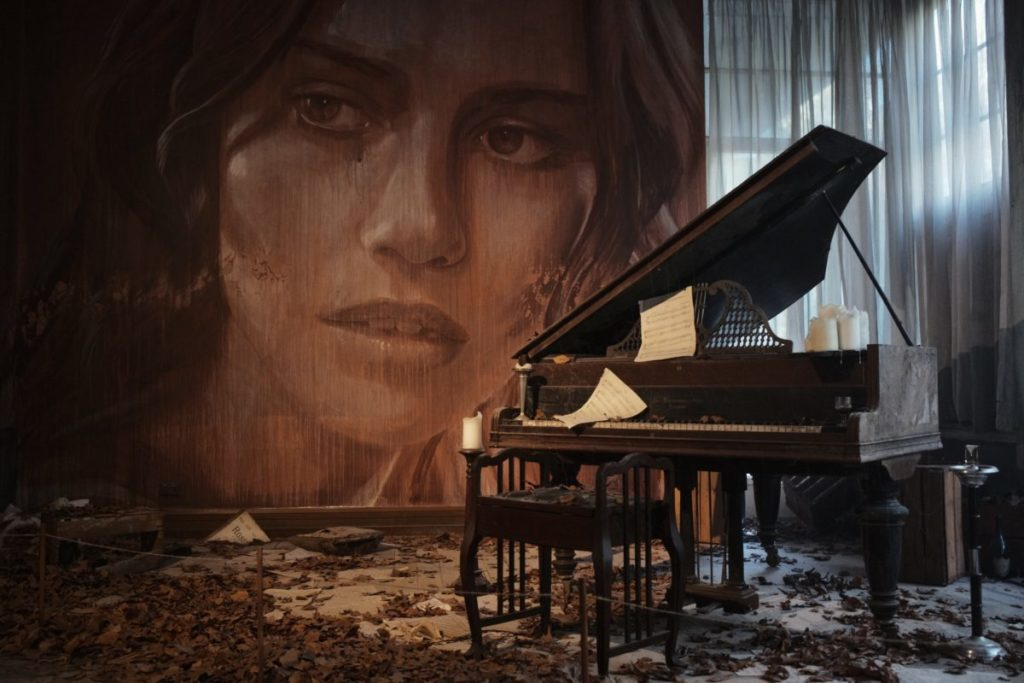 Piano in foreground, Large painting of woman in background