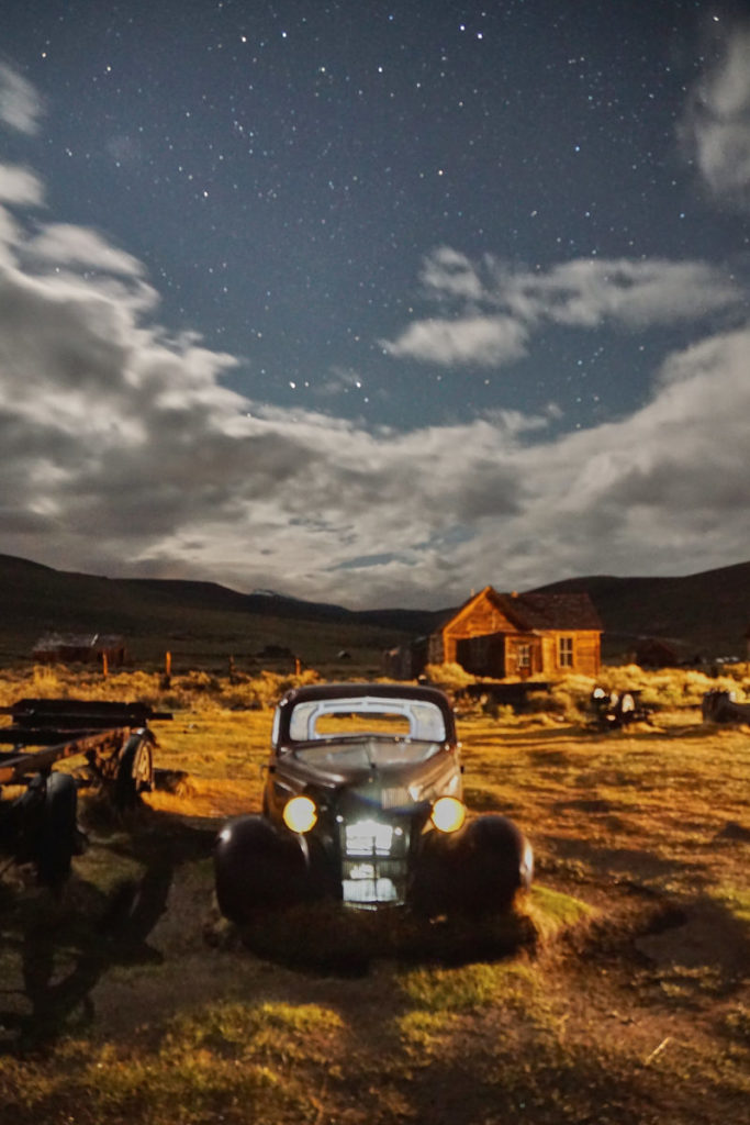 old car with headlights on with desert background